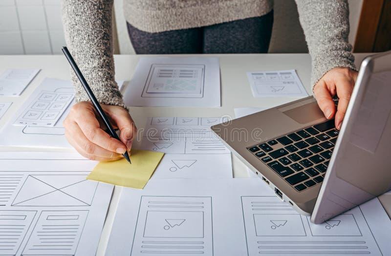 工作在膝上型计算机和网站wireframe剪影的网设计师 免版税库存照片