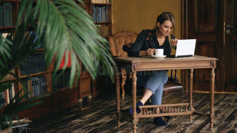 工作在膝上型计算机和饮料咖啡的微笑的学生女孩在大学图书馆里户内 免版税库存照片