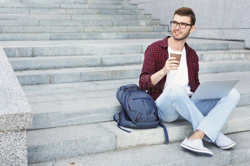 工作在膝上型计算机和饮用的咖啡的学生 免版税图库摄影