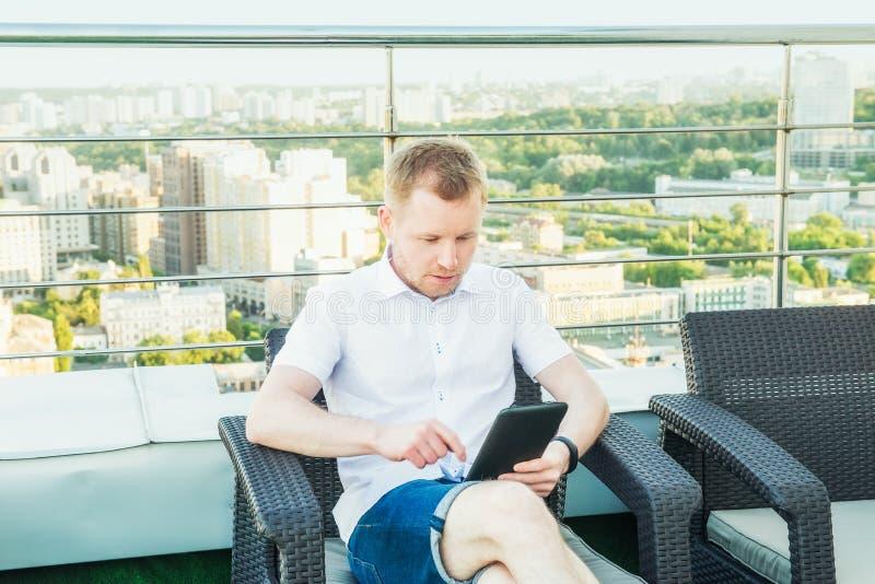 工作在膝上型计算机片剂的年轻商人舒适地坐在办公室大阳台阳台的椅子有都市风景后面的 免版税库存照片