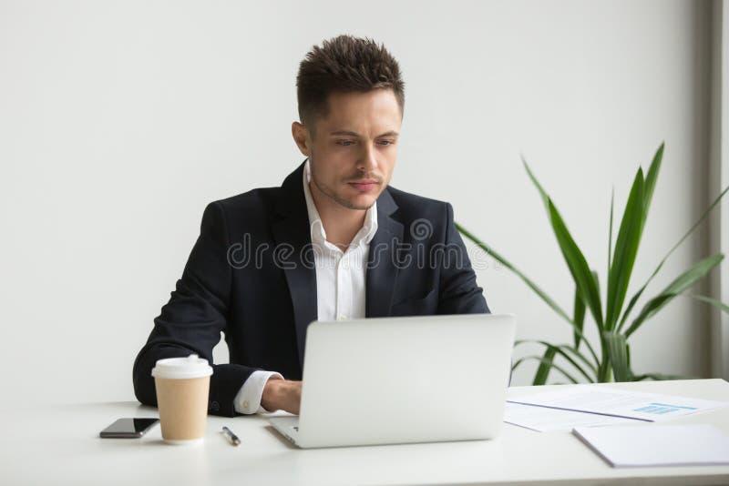 工作在膝上型计算机的严肃的商人 免版税库存照片