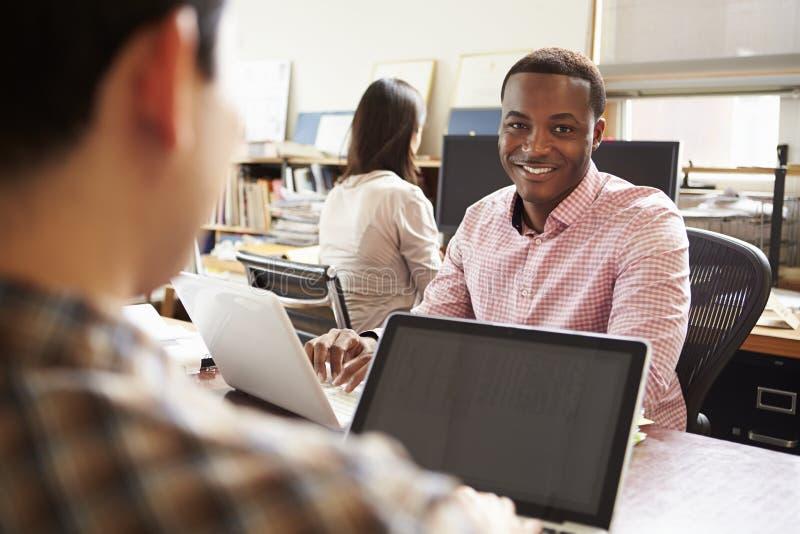 工作在膝上型计算机的书桌的男性建筑师 免版税库存图片