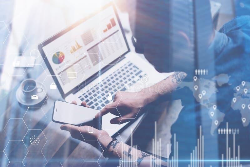工作在膝上型计算机的办公室的商人 人在手上的拿着智能手机 数字式屏幕,虚拟连接的概念 免版税库存图片