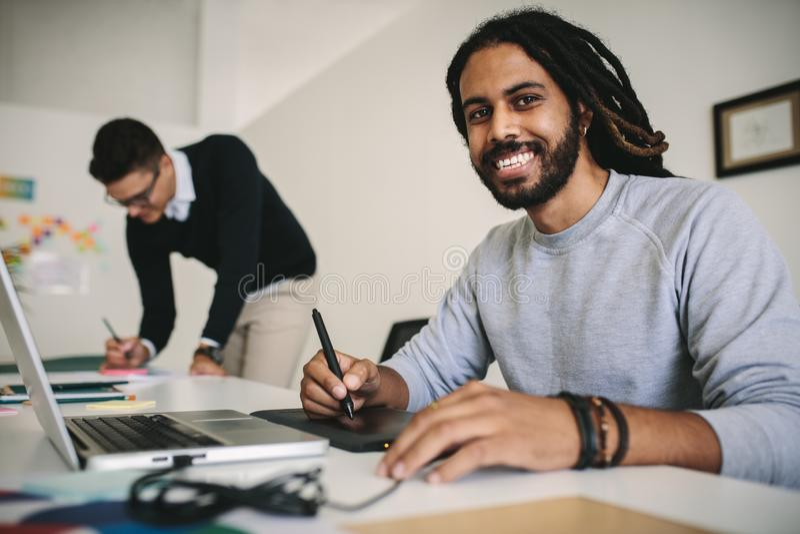 工作在膝上型计算机的办公室的微笑的商人使用digita 免版税库存图片
