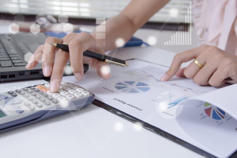 工作在膝上型计算机的办公室的年轻金融市场分析家,当坐在白色桌上时 商人分析文件 库存图片