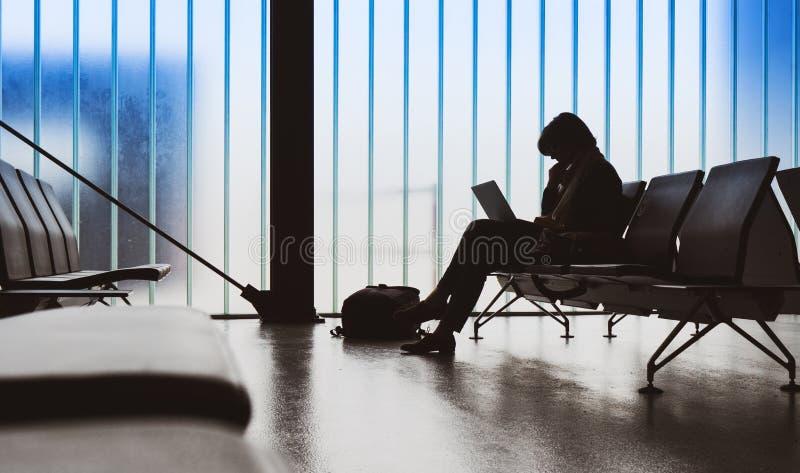 工作在膝上型计算机的女商人在机场终端 图库摄影