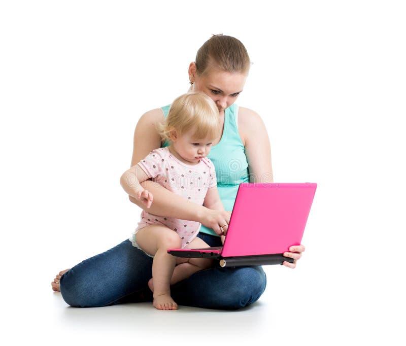 工作在膝上型计算机的母亲和婴孩 免版税库存照片
