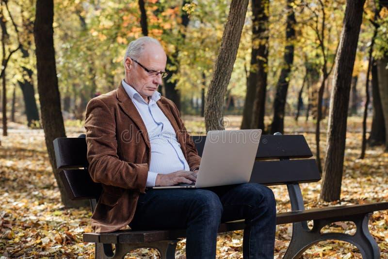 工作在膝上型计算机的老商人外面在长凳 免版税库存照片