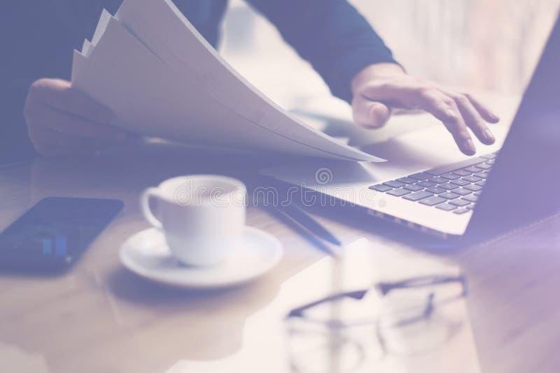 工作在膝上型计算机的晴朗的办公室的商人,当坐在木桌上时 人在手上的拿着纸张文件 免版税库存图片