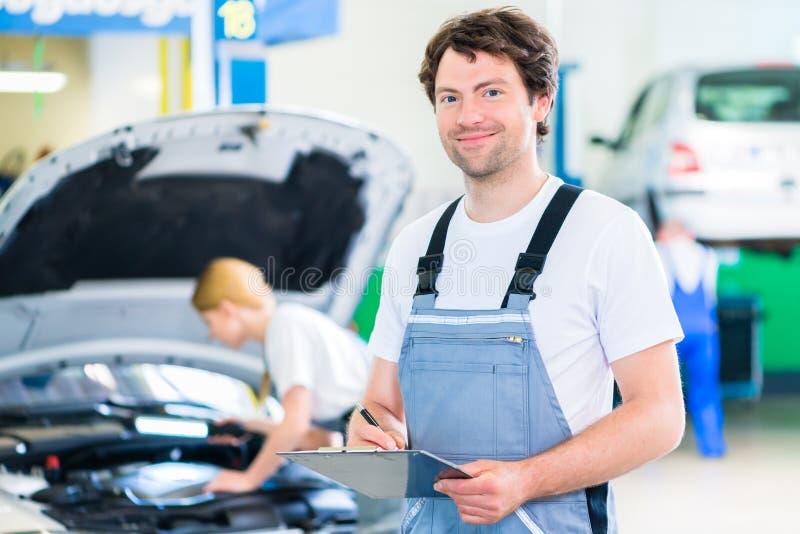 工作在自动车间的汽车修理师队 库存照片