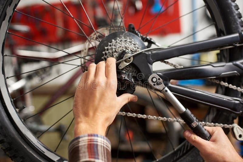 工作在自行车维修车间的男性技工使用工具 库存照片