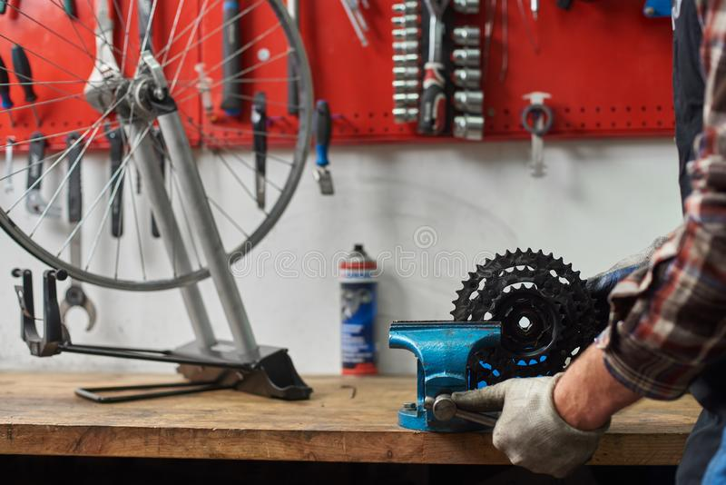 工作在自行车维修车间的男性技工使用工具 库存图片