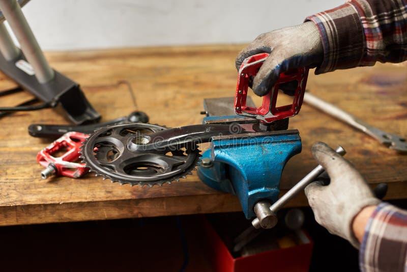 工作在自行车维修车间的男性技工使用工具 免版税库存图片