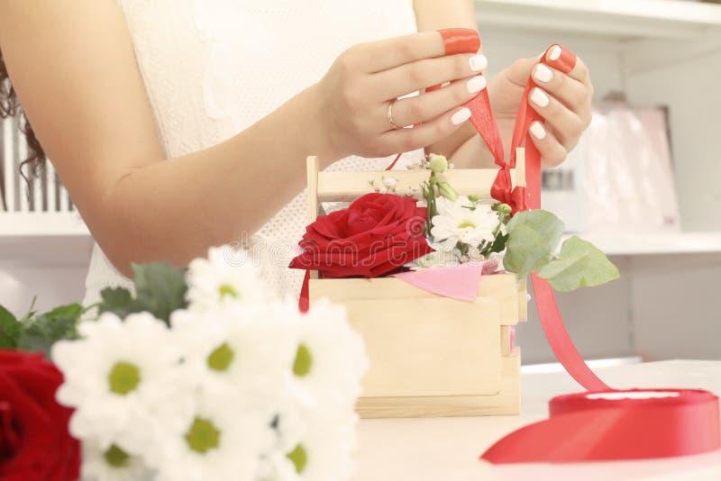 工作在花店的卖花人女孩 在箱子,包裹在装饰纸或安置的新鲜的春天花软的树荫 Floristr 免版税库存图片