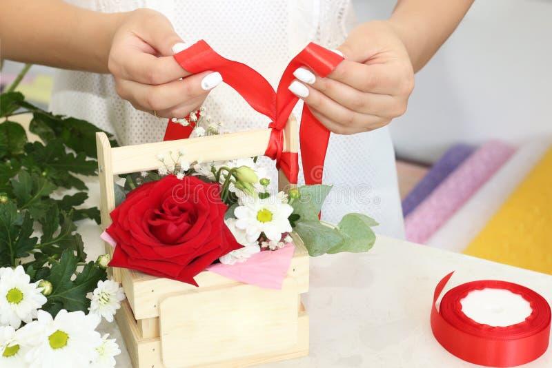 工作在花店的卖花人女孩 在箱子,包裹在装饰纸或安置的新鲜的春天花软的树荫 Floristr 免版税库存照片