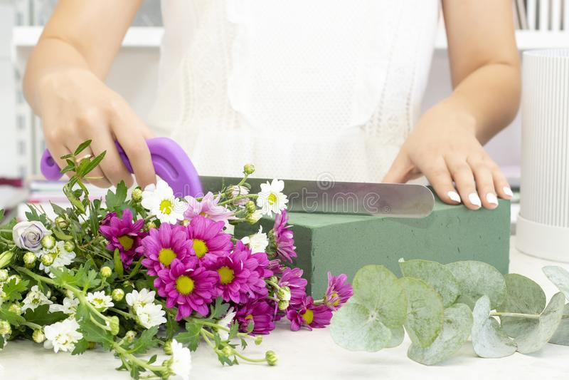 工作在花店的卖花人女孩 新鲜的春天花软的树荫,包裹在装饰纸 Floristry?? ?? 免版税库存照片