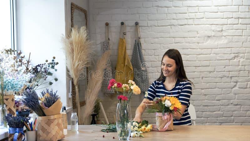 工作在花店的年轻女人 免版税库存照片