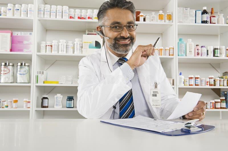 工作在药房的男性药剂师 免版税库存图片