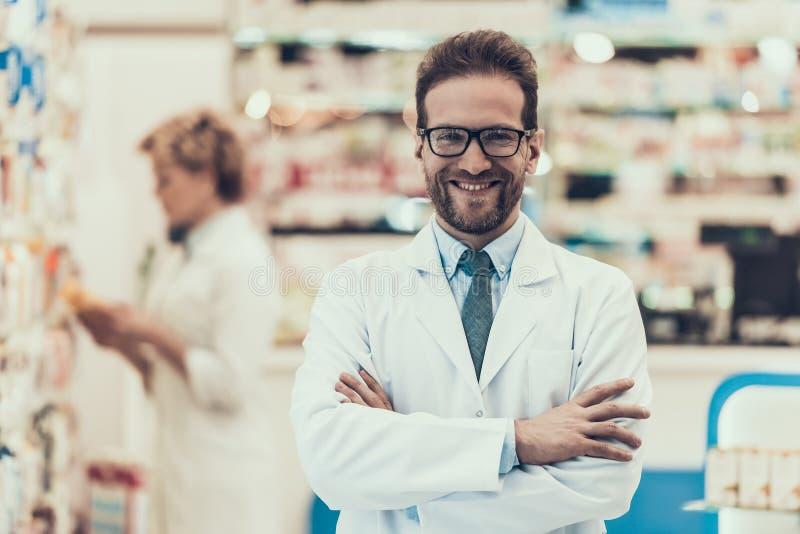 工作在药房的画象微笑的药剂师 免版税库存照片