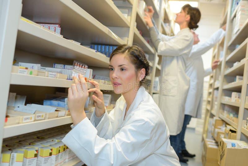 工作在药房药房的两名药剂师化学家妇女 免版税库存图片