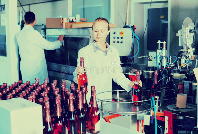 工作在葡萄酒酿造的最后的部分的妇女在工厂的 免版税库存图片