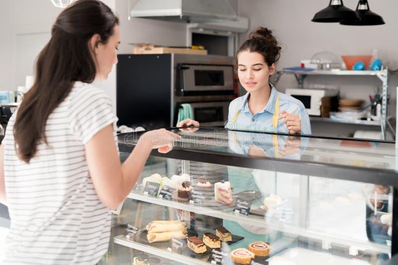 工作在蛋糕商店的少妇 免版税库存图片