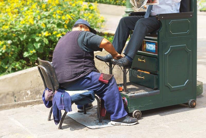 工作在街道上的擦鞋童人擦亮读日报的商人鞋子 利马秘鲁 免版税图库摄影