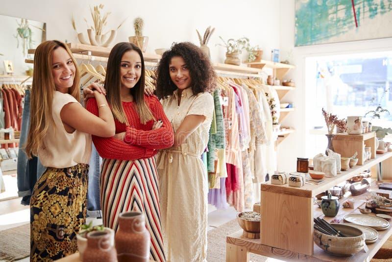 工作在衣物和礼品店的三个女性销售助理画象  库存图片
