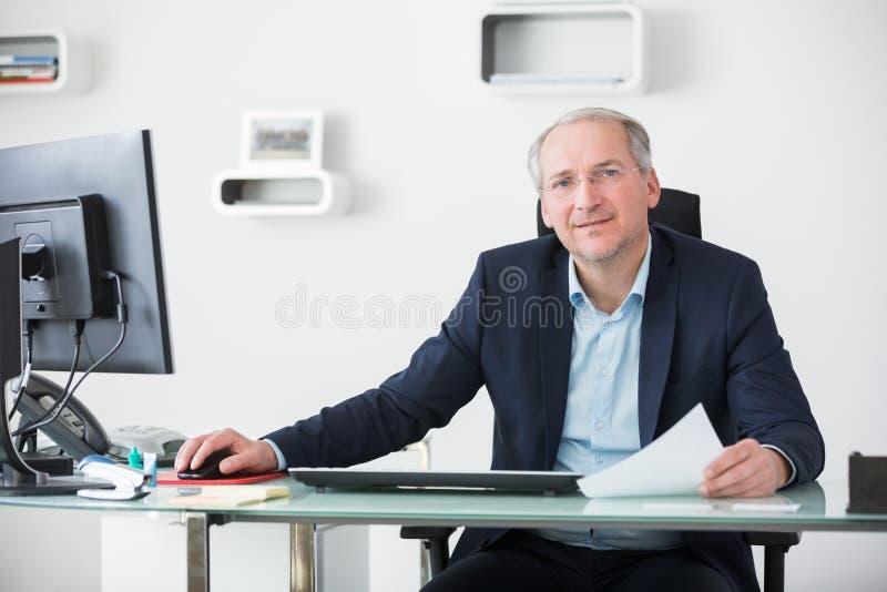 工作在表上的确信的资深商人在办公室 免版税库存照片