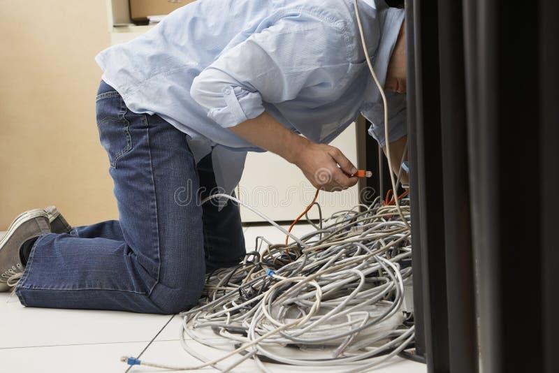 工作在被缠结的计算机导线的人 免版税库存照片