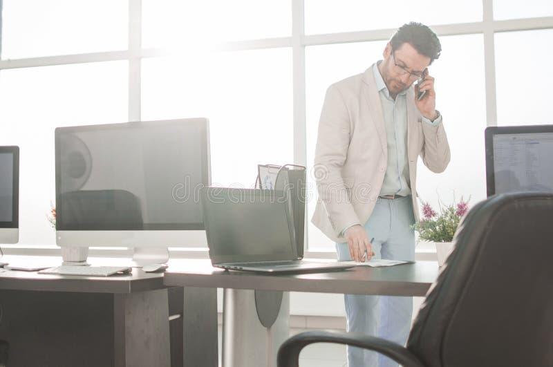 工作在计算器的商人站立在一个明亮的办公室 库存照片