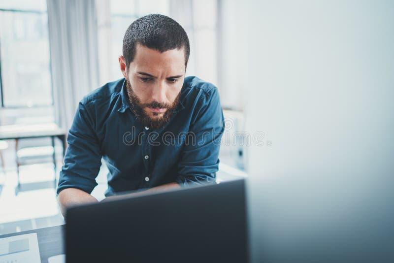 工作在计算机上的lightful办公室的年轻商人,当坐在木桌上时 免版税图库摄影