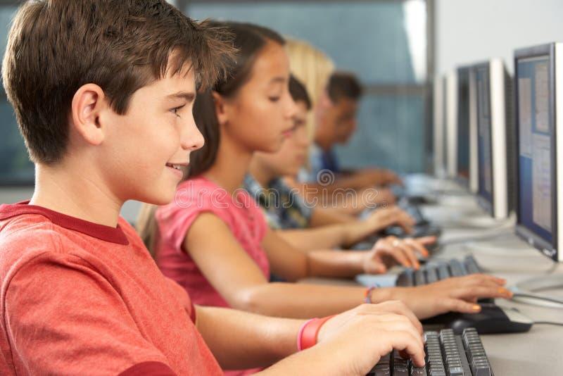 工作在计算机的基本的学生在教室 免版税图库摄影