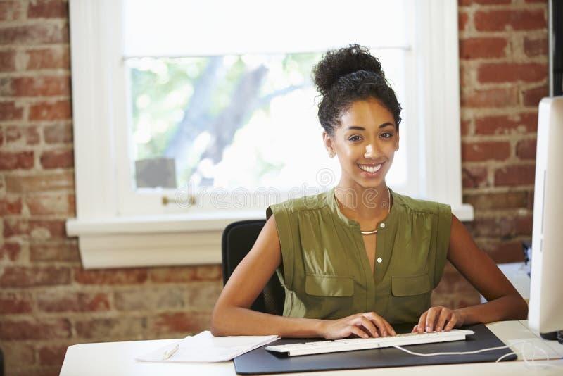 工作在计算机的妇女在当代办公室 图库摄影
