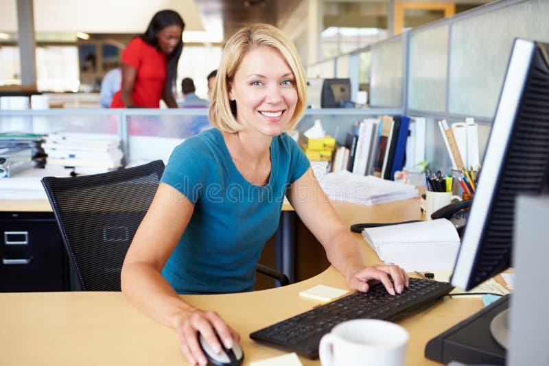 工作在计算机的妇女在现代办公室 免版税图库摄影