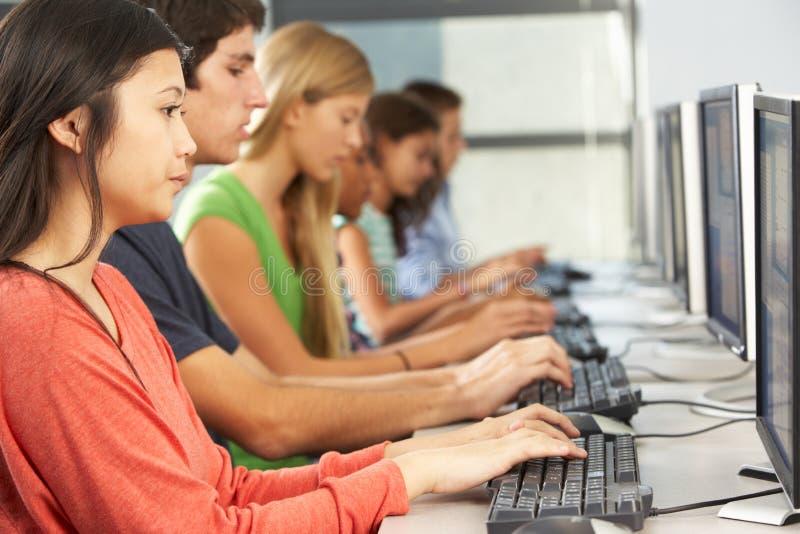 工作在计算机的小组学生在教室 免版税库存照片