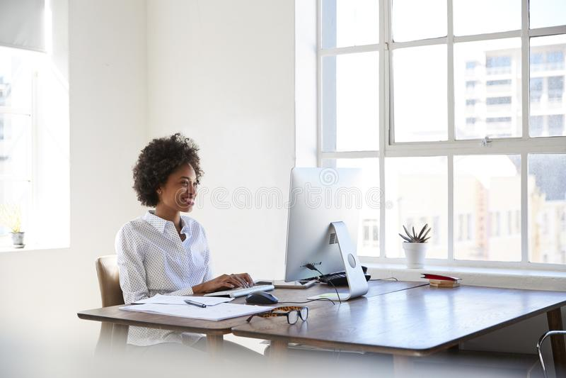 工作在计算机的年轻黑人妇女在办公室 库存照片