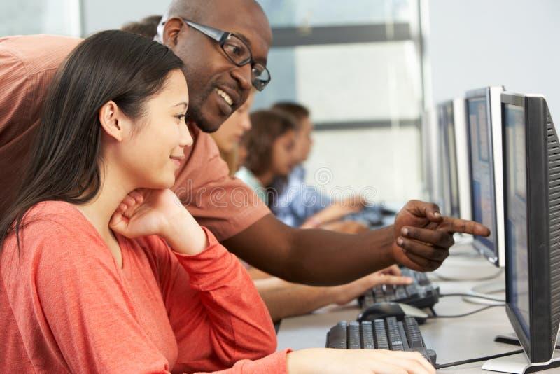 工作在计算机的老师帮助的学生在教室