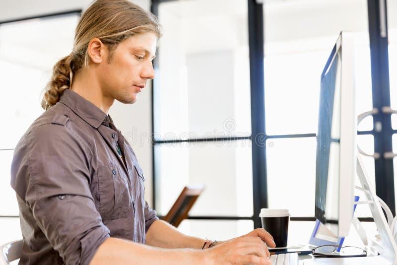 工作在计算机的英俊的商人 库存照片