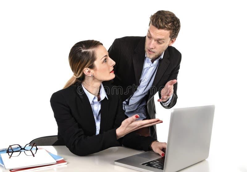 工作在计算机膝上型计算机的年轻可爱的女实业家在办公室争论与重音的工作同事 免版税图库摄影
