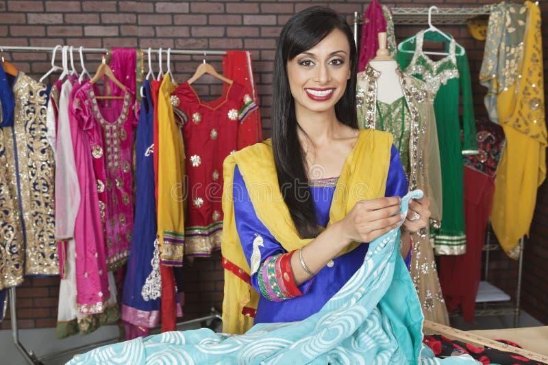 工作在设计演播室的印地安女性裁缝的画象 库存照片
