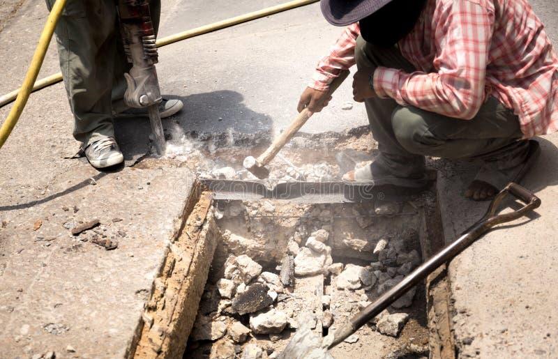 工作在路站点的工作者拆毁与气动力学的苦干的人的沥青 库存照片