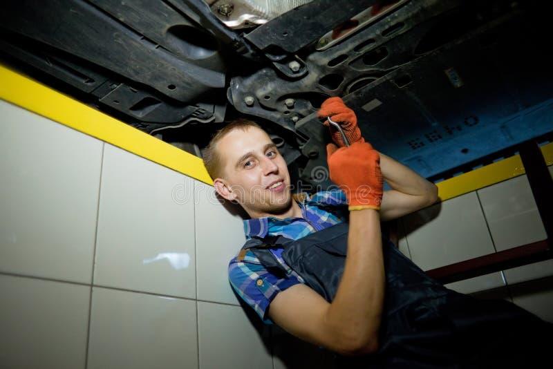 工作在车库的汽车机械师 免版税库存图片