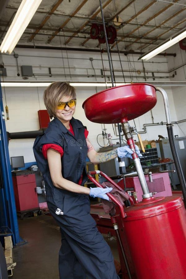 工作在车库的焊接器材的一位愉快的女性技工的画象 免版税图库摄影
