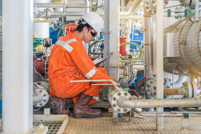 工作在近海油和煤气中央设施的电工和仪器技术员,当检查原油水平时 库存图片