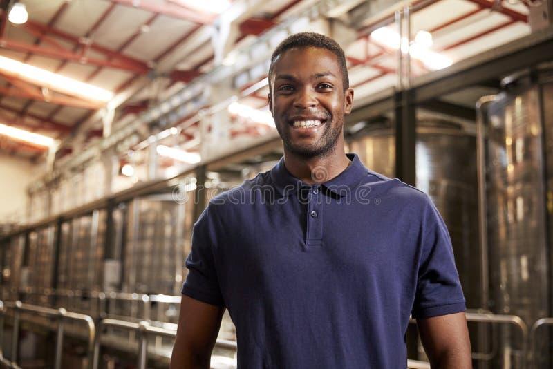 工作在酒工厂的一个年轻黑人的画象 免版税库存照片