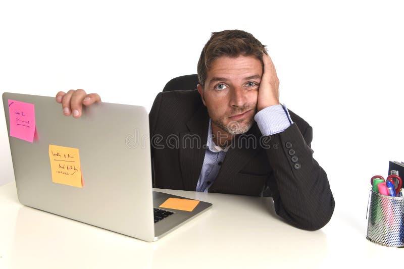 工作在重音的疲乏的被浪费的商人在办公室便携式计算机用尽了淹没 免版税库存图片