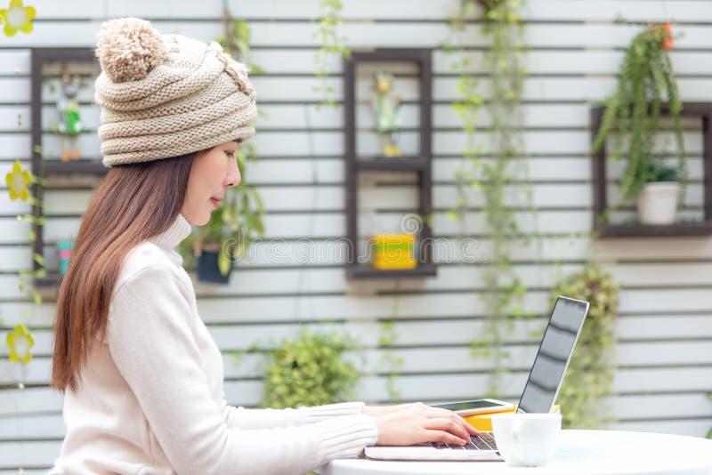 工作在键盘的亚裔妇女 工作区放松在办公室的庭院里使工作和设计有平均观测距离的膝上型计算机智能手机变冷 免版税库存图片
