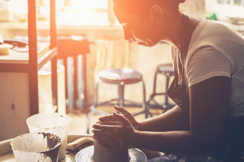 工作在陶瓷工` s轮子的年轻女性陶瓷工 免版税库存照片