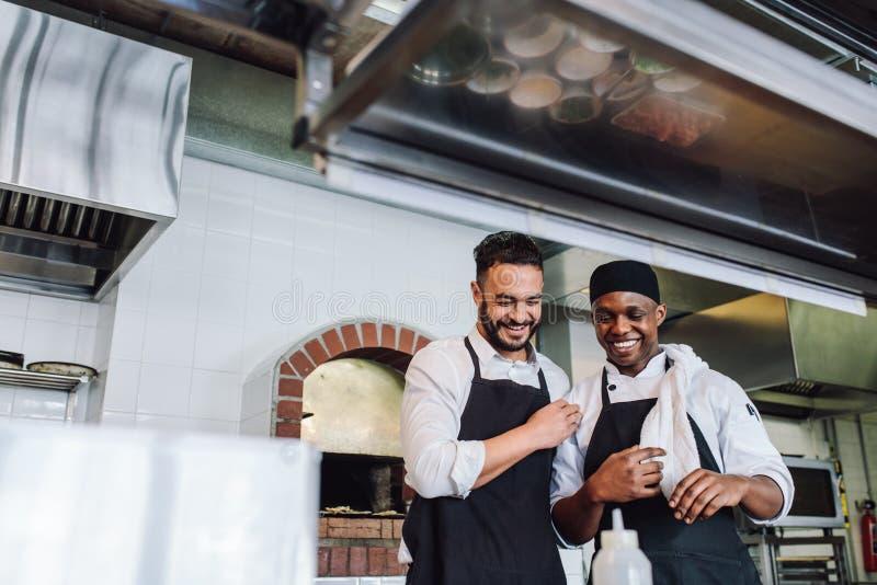 工作在餐馆厨房里的微笑的专业厨师 免版税库存照片